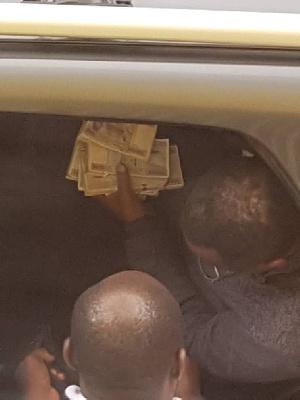 Maurice Kamto dans sa voiture, tenant des liasses de billets