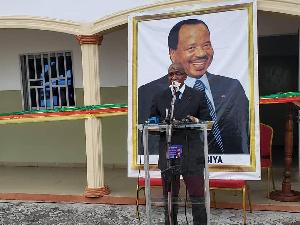 Dr Malachie, derrière lui, une photo de Paul Biya