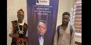 Arol Ketch et un autre activiste à coté d'une photo de Mongo Beti