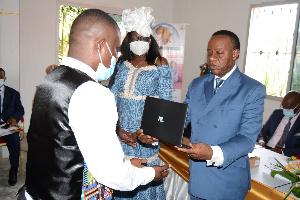 Fame Ndongo remettant un ordinateur à un étudiant