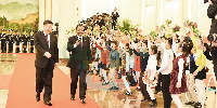 Les président chinois et camerounais défilant devant des enfants chinois
